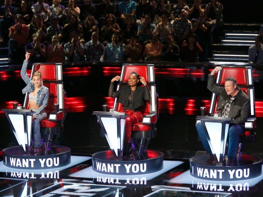 """Blake Shelton (right) uses his signature move to convince a contestant to pick him as their coach during Season 13 of """"The Voice."""" Miley Cyrus (left) and Jennifer Hudson joined Shelton and Adam Levine (not pictured) as coaches in 2017."""