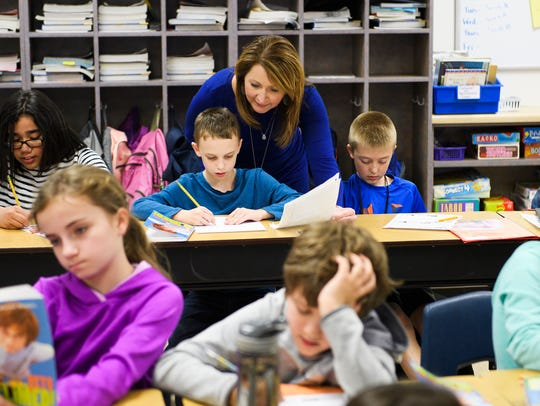 Suzanne Billings helps her fourth grade students with