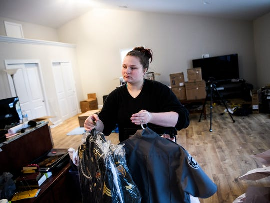 Elizabeth Hills moves some of her husband Aaron's military suits as they begin to move into their new home in Boiling Springs on Tuesday, March 6, 2018.