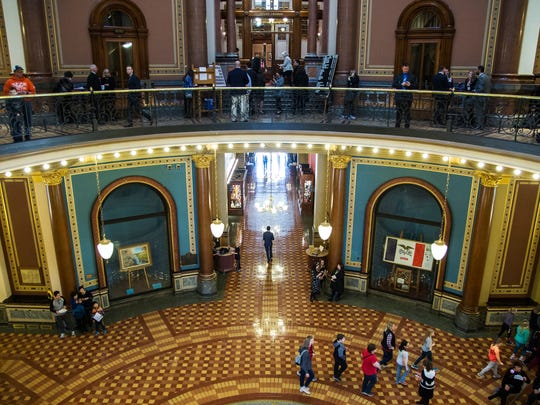Tour groups, politicians and lobbyists walk past the doors to the senate chamber on Tuesday, March 13, 2018, in the Iowa State Capitol.