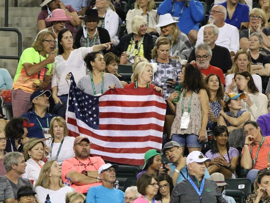 Serena Williams and Venus Williams fans hold an American