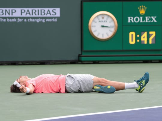 David Ferrer falls to the court after diving for a
