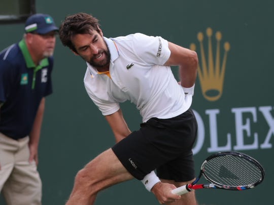 Jeremy Chardy successfully returns a ball through his legs to Roger Federer at the BNP Paribas Open, Wednesday, March 14, 2018.