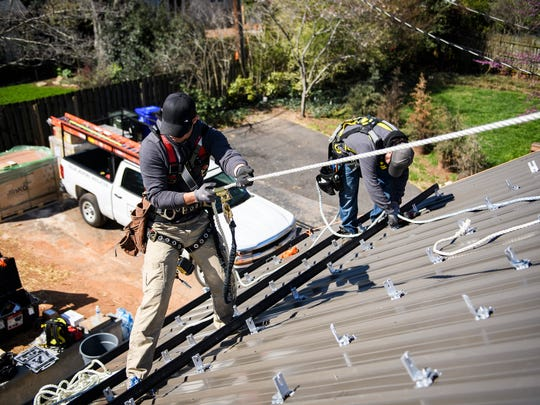 Summit Solar workers Ryan Phillips and Nick Messer start to install solar panels on the roof of a home on Thursday, March 15, 2018.