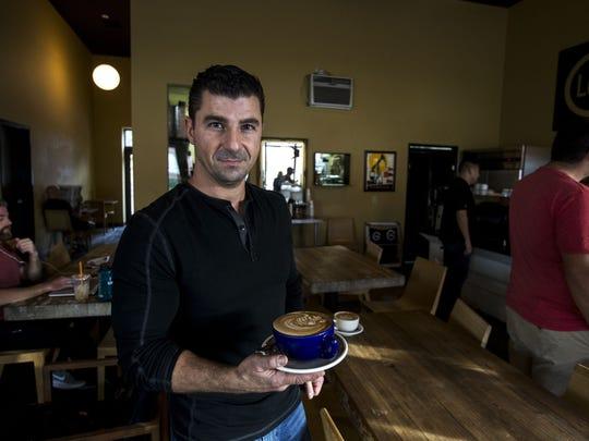 Owner Daniel Wayne holds a latte at Lola Coffee in Phoenix