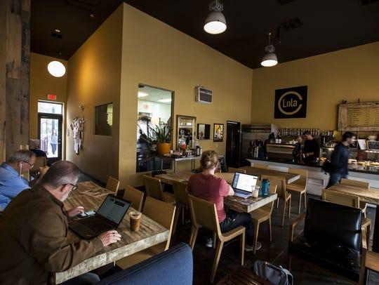 Customers work at Lola Coffee in Phoenix.