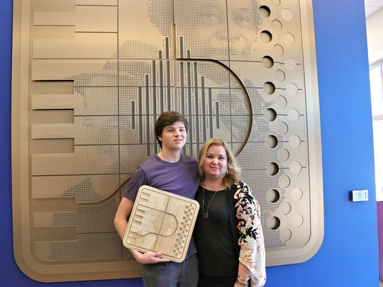 Reuben and Rhonda Egan stand in front of new artwork in the Festival International office in downtown Lafayette.Friday, March23, 2018