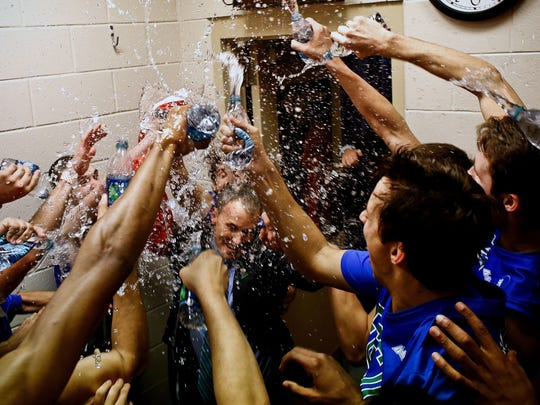 FGCU shower their coach Andy Enfield with water in