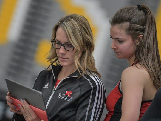 Kimberly assistant coach Kayla Fink goes over video of a high jump by Emily Scott during the Oshkosh High School Invitational Big School track meet March 26.