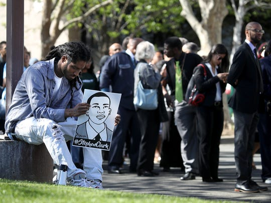 Steven Ash holds a sign with an image of Stephon Clark