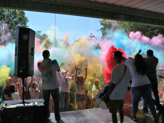 Holi Festival attendees are covered in colored powder at the Lafayette Holi Festival on Saturday.