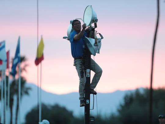 A worker raises lights for the fourth playoff round