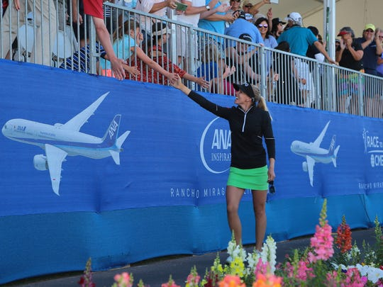 Pernilla Lindberg high fives fans on her walk to Poppie's Pond after winning the ANA Inspiration in eight playoff rounds, Rancho Mirage, Calif., Monday, April 2, 2018.