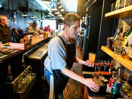Waitress Kristi Sanders serves up a couple Amaretto Sours at Henderson's historic Metzger's Tavern that has reopened under new management and a smoke-free atmosphere.