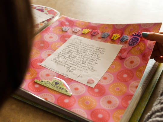 Jacalyn Lambrix, 15,  looks at childhood memory books with her family at their home in Mulliken Friday, April 6, 2018.  Jacalyn has had two bouts with kidney cancer as a child.  She was diagnosed with Wilm's tumor, a kidney cancer when she was six.  She has been cancer-free for five years.