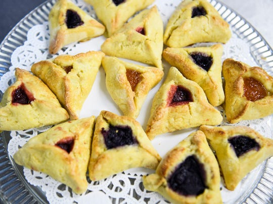 A plate with an assortment of blueberry, strawberry and apricot Hamantaschen cookies, a traditional Jewish treat, sit on a plate at the Temple of Israel on Friday, March 16, 2018.