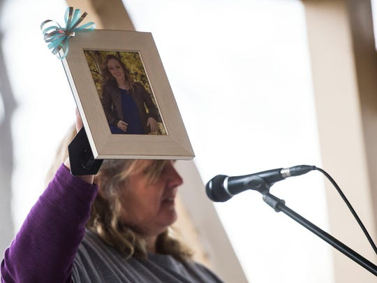 Ann Marie Doolittle hold up a photo of her daughter Ashley Doolittle, who was murdered by her ex-boyfriend in June of 2016, while speaking about her experience at the Eighth Judicial District's walk for National Crime Victims' Rights Week on Thursday, April 12, 2018, at City Park in Fort Collins, Colo.