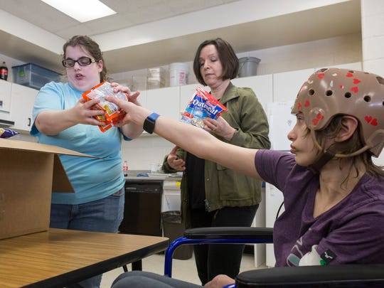 Junior Zoey Young, 16, left, paraprofessional Julie Badge and junior Sidney Jamison, 16, work together to fill a box with donated food and goods to be given to a family in need at Franklin High School in Livonia on Wednesday, March 21, 2018.
