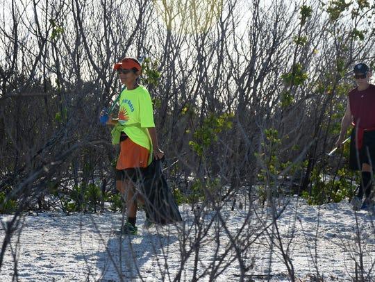 File: Maria and Charles Lamb hunt for trash at at Tigertail Beach on Marco Island.