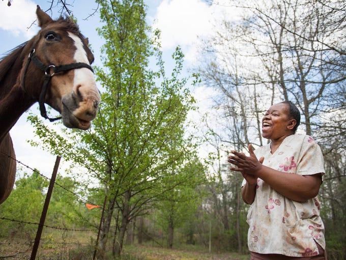 Doris Durham visits Fancy, the neighborhood horse,