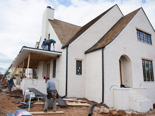 Construction workers work on one of the homes in the