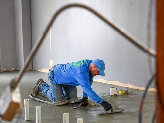 "Framed by a piece of electrical conduct, Scott Busby, with Garrett Concrete, works on a new concrete floor as renovations of the Soaper Hotel's first floor continue for a new restaurant called ""Hometown Roots"" that plan will open later this summer Thursday, April 26, 2018."