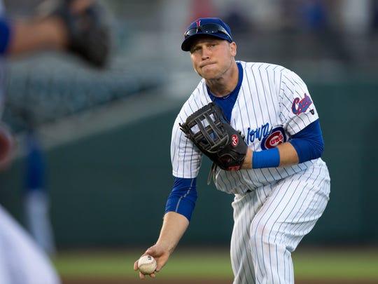 Iowa Cubs' Chris Valaika (4) throws the ball to first