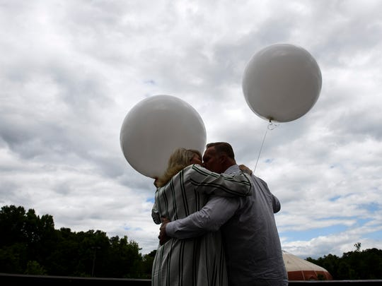 Pastors Ron and Hope Carpenter share a kiss before releasing balloons to say their goodbyes to Redemption Church on Sunday, May 6, 2018 before their move to San Jose, Calif.