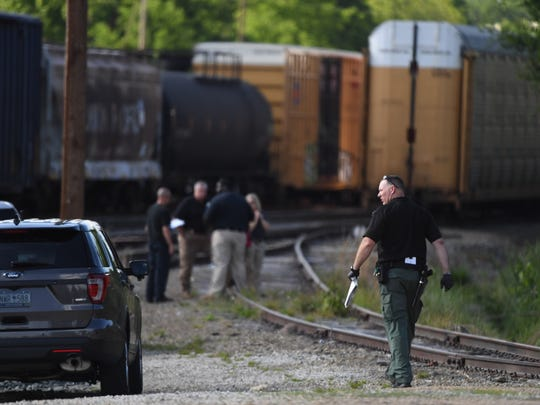 Officials work near the scene where the body of a woman was found after she was struck by a cargo train near the Amtrak station in Greenville on Tuesday, May 8, 2018.