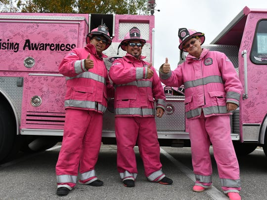 Firefighters Alex Delgado, from left, Juan Perez and Joe Wise are in the pink with their truck covered by thousands of signatures. With almost 200 people under 200 pink umbrellas, the Partners for Breast Cancer Care created a massive pink ribbon in a parking lot at Miromar Outlets on Saturday morning. The organization provides no-cost breast screening, diagnostic testing, surgery and treatment to low-income, uninsured women and men of any age.