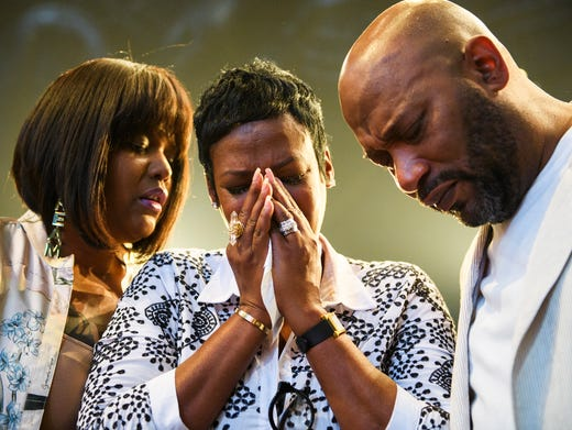 Queenie Freeman, middle, prays with Aventer Gray, left,