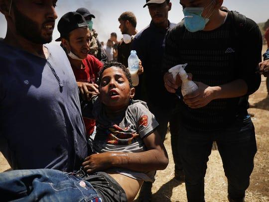 Un niño herido es cargado en brazos en las protestas de palestinos.