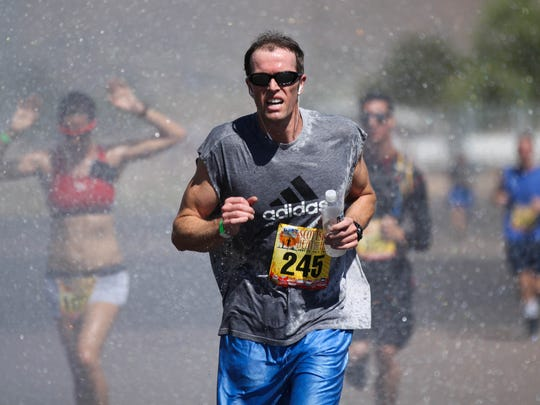 Participants run through water sprayed by a Scottsdale Fire Department firetruck during  the first Beat the Heat race at WestWorld in Scottsdale on June 22, 2013.