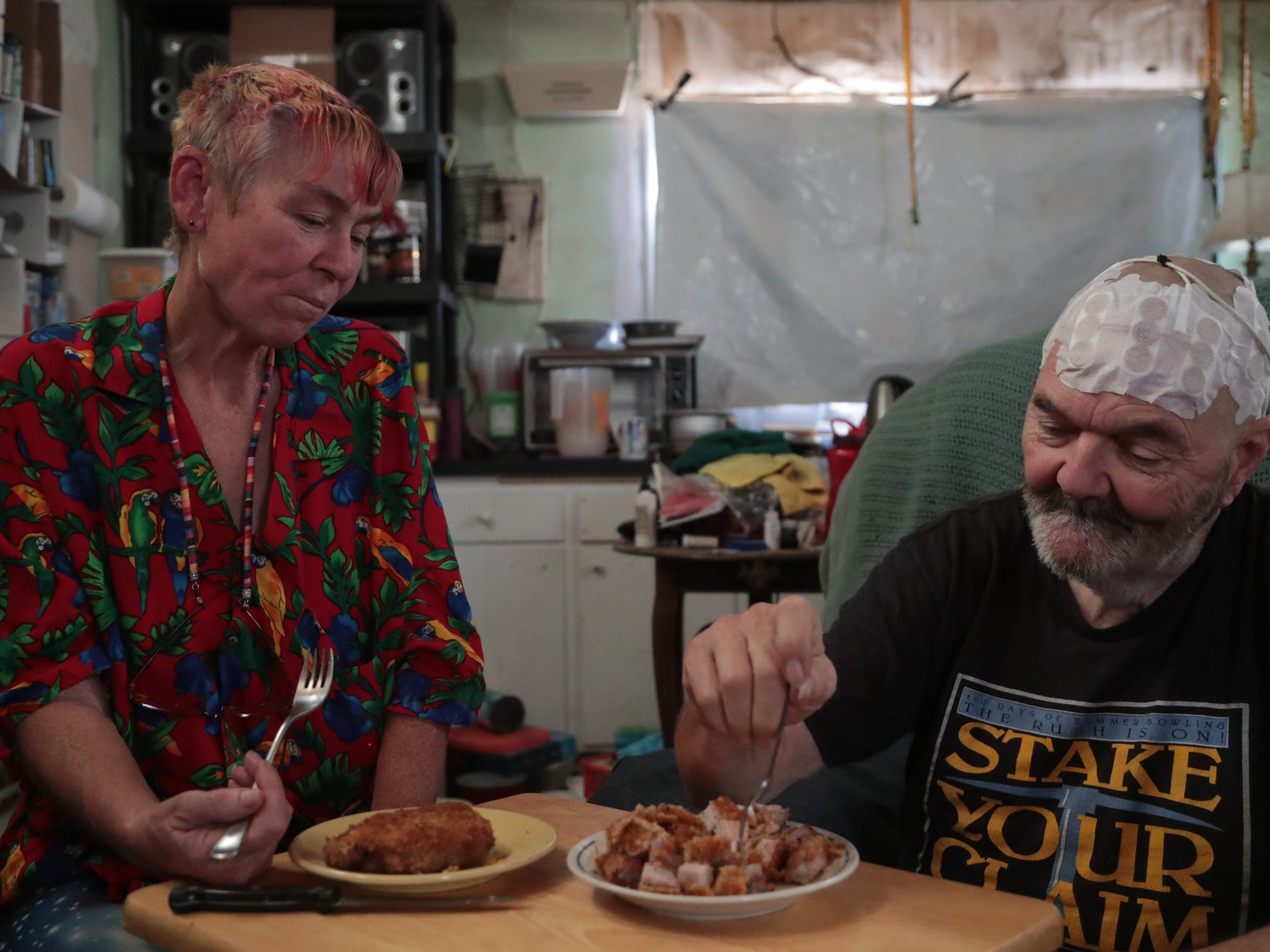 Zena Awesome eats fried pork chops for lunch with her husband Vandar in their Wonder Valley home. She cuts his into small pieces, because he does not have teeth.