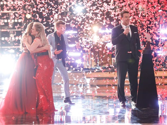 """""""The Voice"""" winner Brynn Cartelli, left, hugs her coach, Kelly Clarkson, as runner-up Britton Buchanan and host Carson Daly stand nearby."""