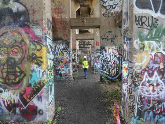 "Jocelyn Gabrynowicz Hill walks the Port Richmond rail yard and ""Graffiti Pier"" in Philadelphia. The popular public art space called Graffiti Pier has been shut down by police over safety concerns, prompting a push to have the former coal pier-turned-outdoor museum made into an official park as a way to save it from the fate of other graffiti meccas that were razed by developers."