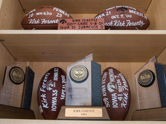Footballs and trophies lines the shelves in Iowa football