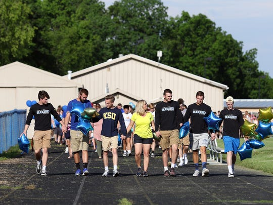 West Muskingum track coach Michele Shirer shares memories with teammates of the late Cameron Strauss during a lap around the West Muskingum High School track in Strauss' honor on Tuesday. Hundreds attended a vigil for Strauss, a 2017 graduate of West Muskingum.