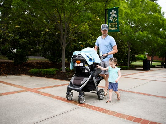 Tim Jones walks through Greer City Park with his daughter