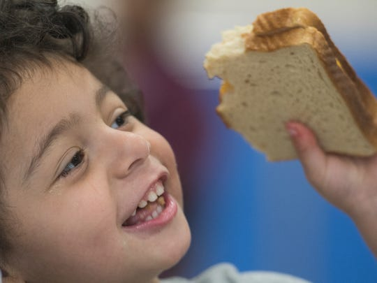 Dilovan Silevani, 3, of Nashville, tends to his sandwich while participating in a summer meals program at Whitsitt Elementary School on Tuesday, June 5, 2018, in Nashville, Tenn.