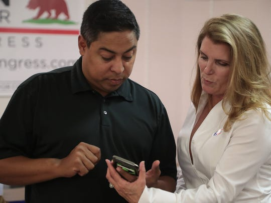 Candidates Kimberlin Brown-Pelzer and Jeff Gonzalez look at initial election results in La Quinta, Calif., Tuesday, June 5, 2018.