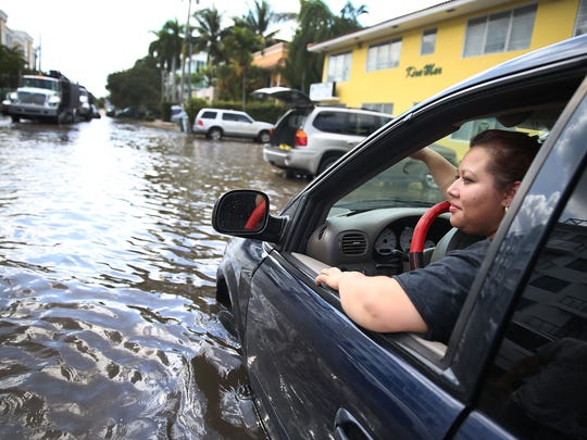 Sandy Garcia sits in her vehicle that was stuck in a flooded street caused by the combination of the lunar orbit which caused seasonal high tides and what many believe is the rising sea levels due to climate change on September 30, 2015 in Fort Lauderdale, Florida.