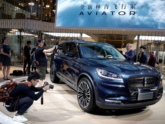 Journalists film the Lincoln Aviator SUV after the