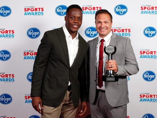 Teddy Bridgewater poses with coach James Moore, accepting the Competitive Cheer Team of the Year award for Bullitt Central, during the 2018 Courier Journal Sports Awards held at The Louisville Palace in downtown Louisville. June 7, 2018