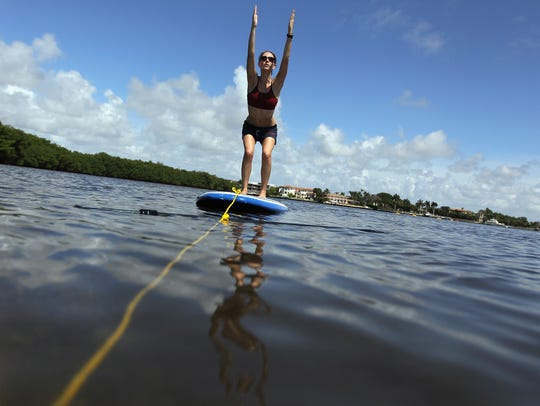 Yoga instructor Sarah Henry leads a class during a paddleboard yoga session at Adventure Sports Miami on July 10, 2011.