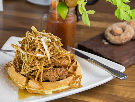 Fried leeks sit atop the chicken and waffles dish at