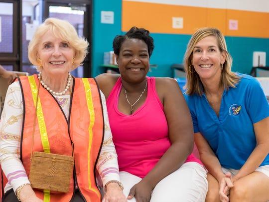 Volunteers Bonnie Wolfarth, left, Latonya Gamble, and