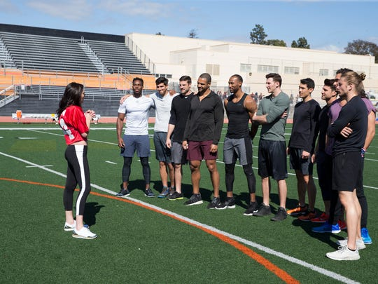 Lincoln Adim (left) runs drills with a group of 'Bachelorette' contestants as Becca Kufrin looks on.