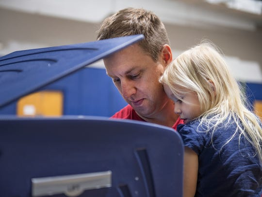 Austin Eidson casts his vote as he holds his daughter,