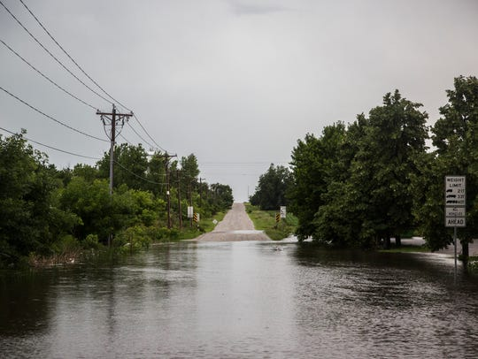 Water flows over 500th Avenue on the western edge of